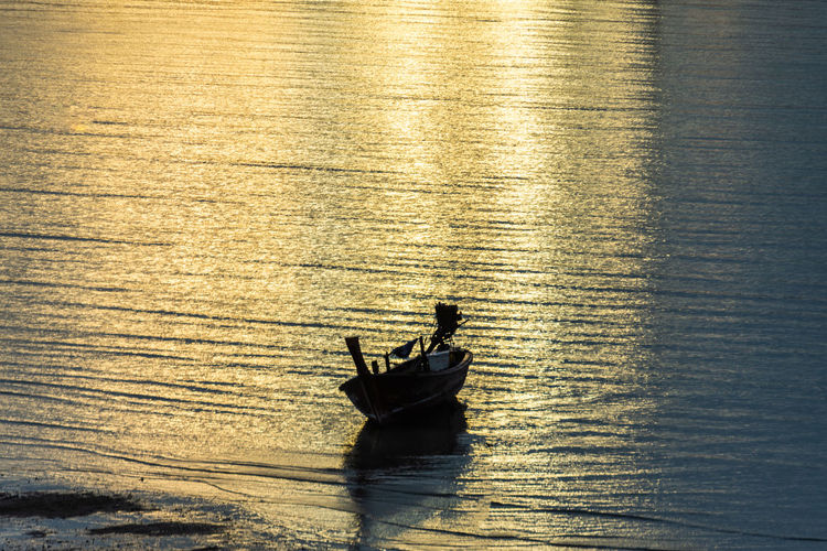 Silhouette man in boat sailing on sea against sky