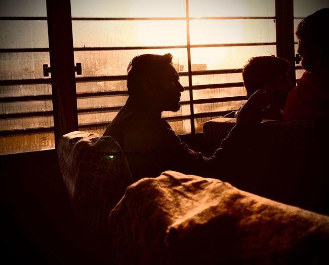 Rear view of people sitting on window