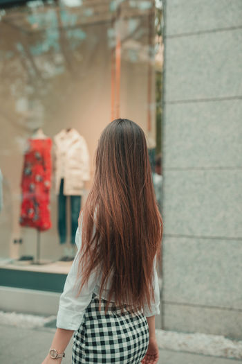 Side view of woman standing on footpath by store window