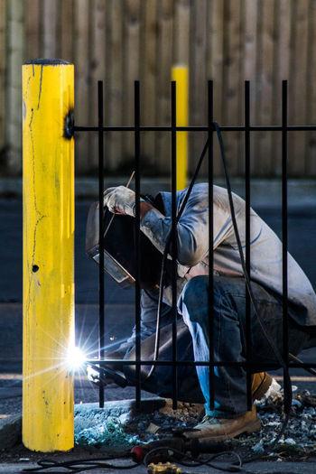 Welder holding mask while welding fence
