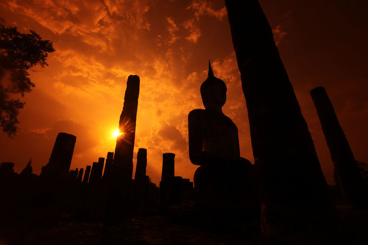 Low Angle View Of Silhouette Buddha Statue At Wat Sa Si During Sunset