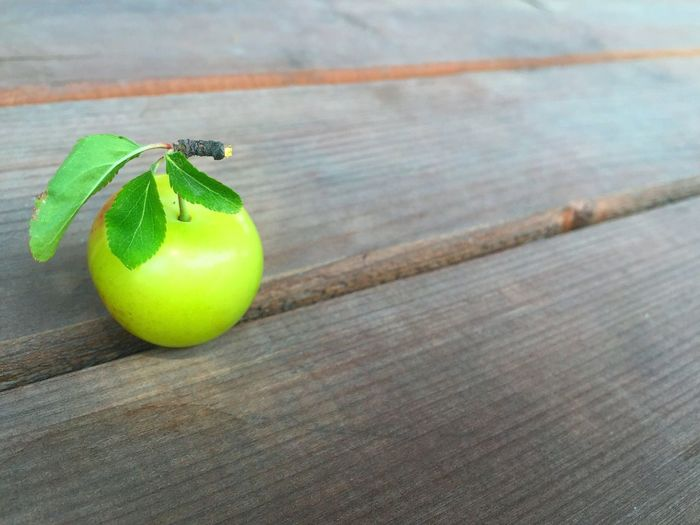High angle view of green plum on hardwood floor