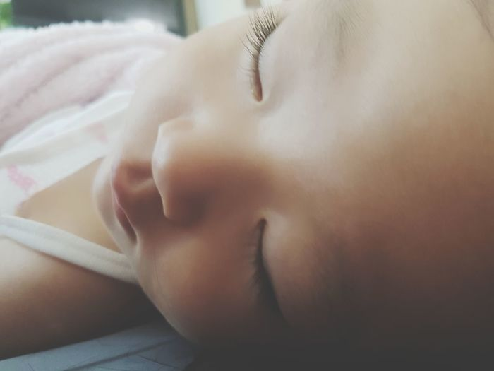 Close-up portrait of baby sleeping on bed