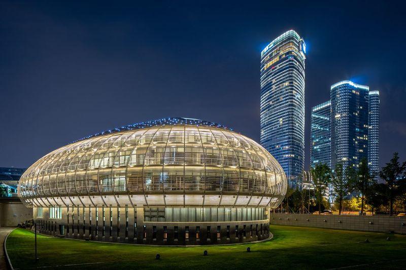 Illuminated modern building against blue sky