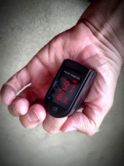 Pulse Oximeter Blood Oxygen Level Close-up Connection Device Focus On Foreground Holding Human Finger Medical Oxygen Person Pulse Oximeter Pulse Rate Technology