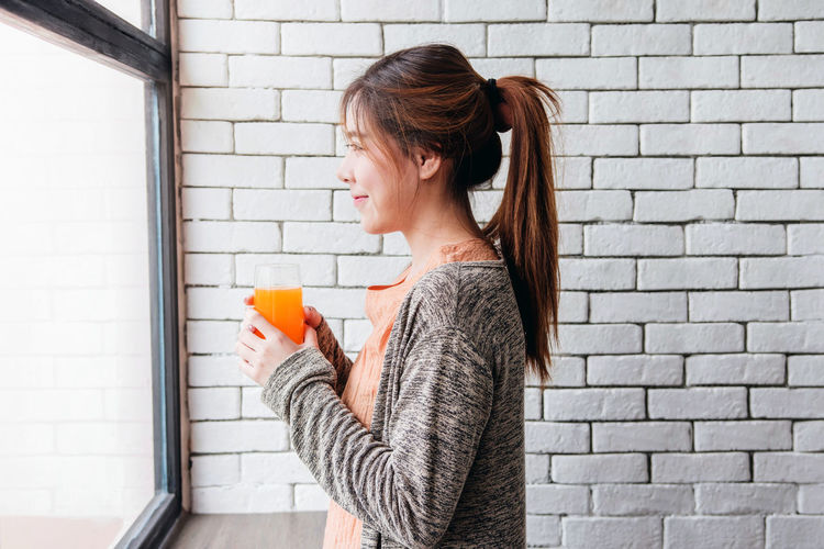 Side View Of Young Woman Holding Drink Glass By Wall