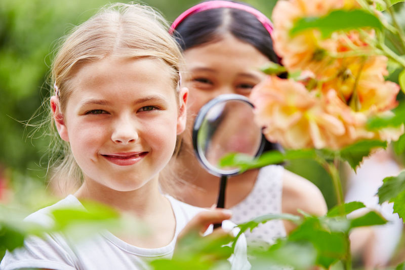 Portrait of cute girls holding magnifying glass by flowering plants