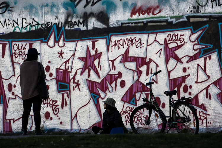Man standing by graffiti on wall in city