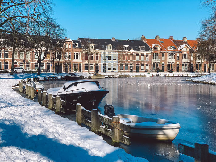 Boats in canal by buildings in city during winter