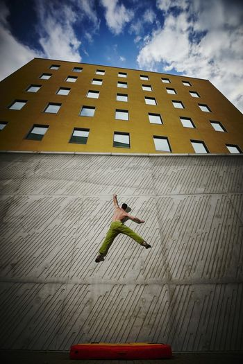 Low angle view of man climbing wall against sky