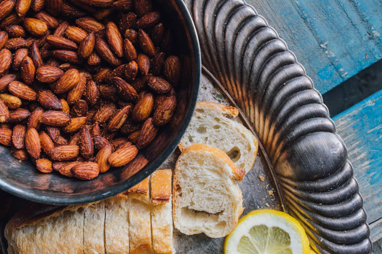 Picnic almonds in silver bowl on silver tray platter with bread, lemon on blue wood