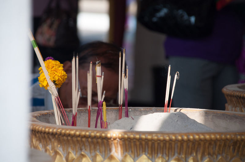 Close-up of burning incense in vase at temple