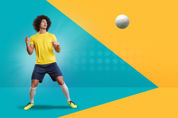 Soccer player looking at ball against colored background