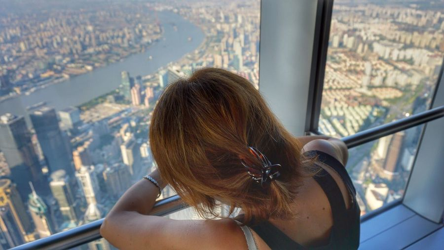 Rear view of woman looking at cityscape through shanghai tower