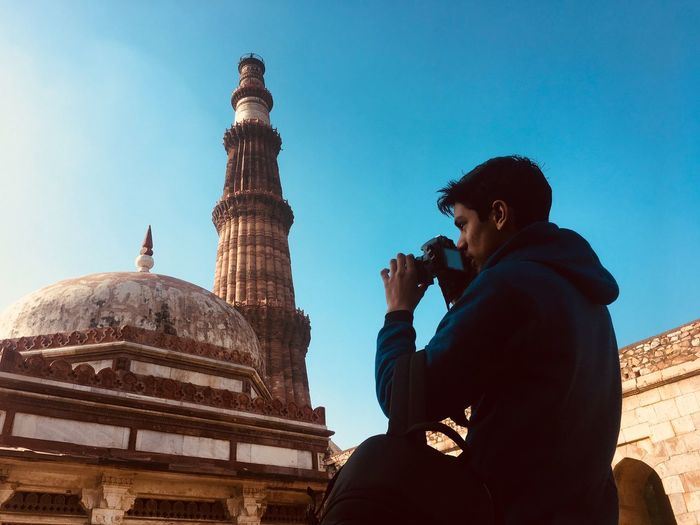 Low angle view of young man photographing mosque against clear blue sky