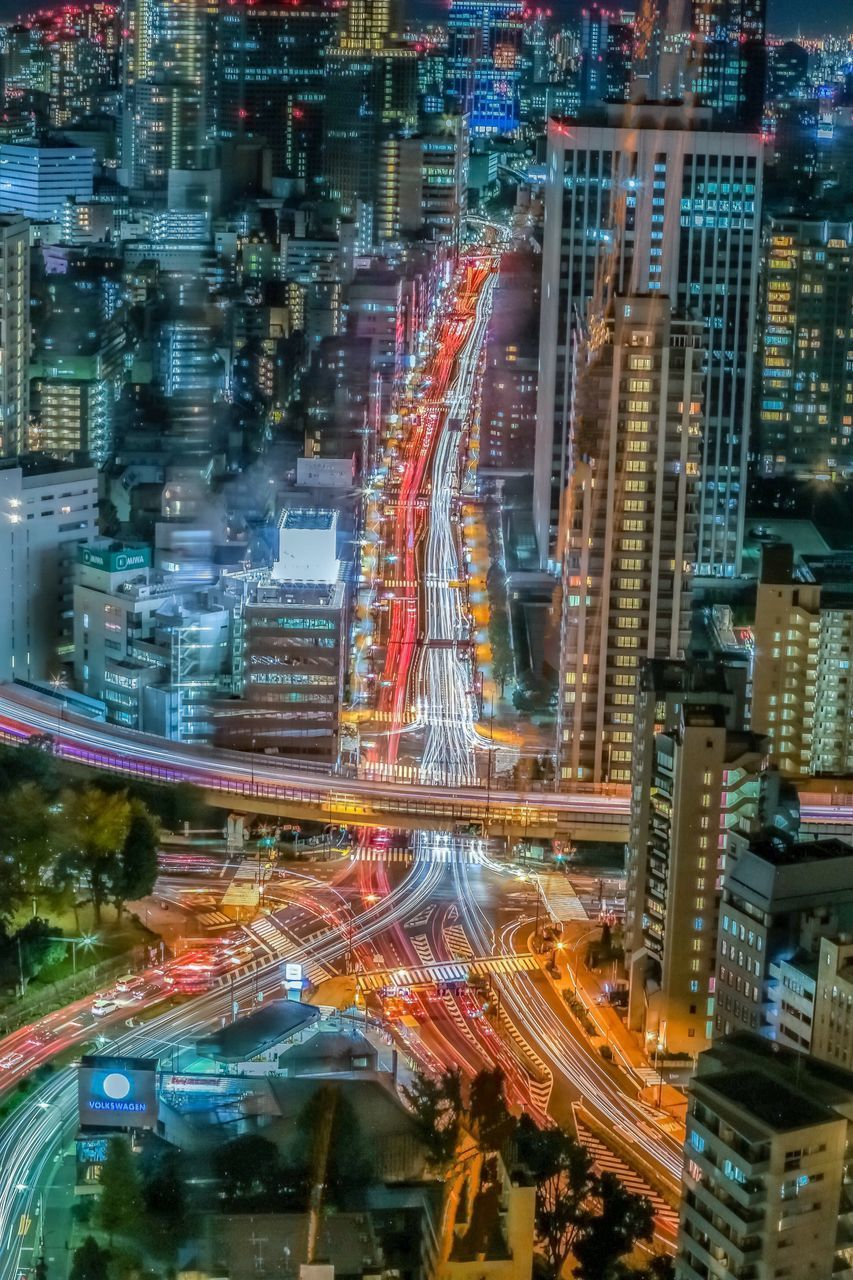 illuminated, city, motion, building exterior, architecture, long exposure, light trail, city life, built structure, night, street, speed, city street, blurred motion, cityscape, no people, transportation, building, office building exterior, modern, skyscraper, digital composite