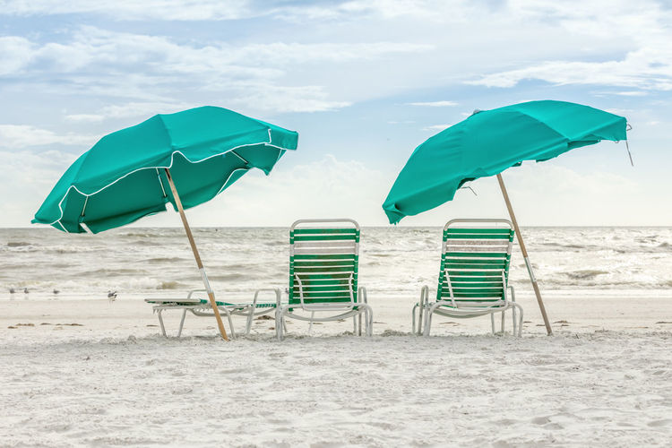 Deck chairs with parasols at beach against sky