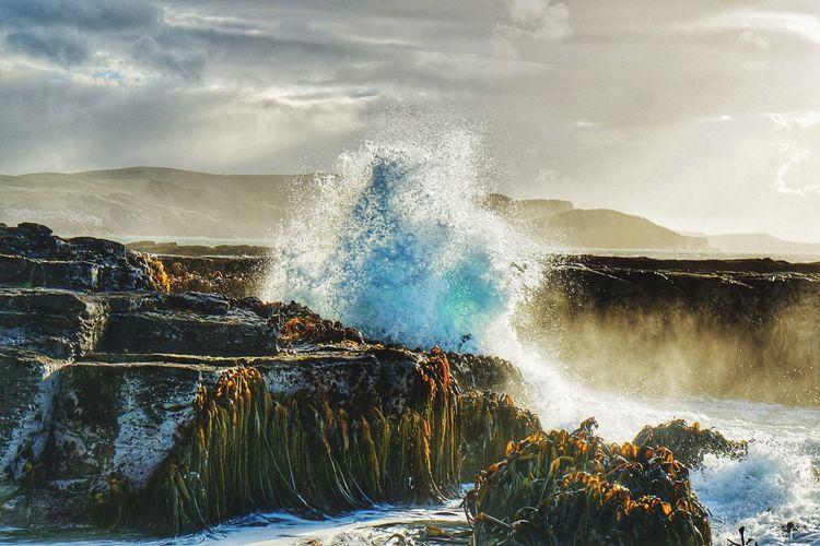 Waves splashing on rocks against the sky