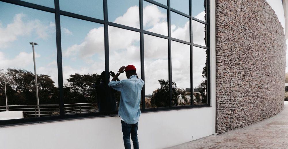 Reflection of man adjusting skull cap on modern building