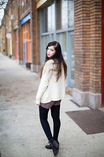 Portrait of young woman walking on footpath in city