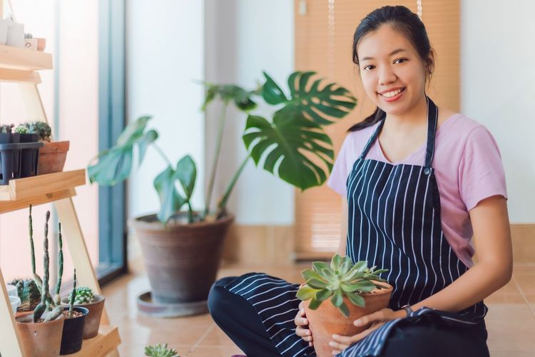 Portrait of young woman standing by potted plants