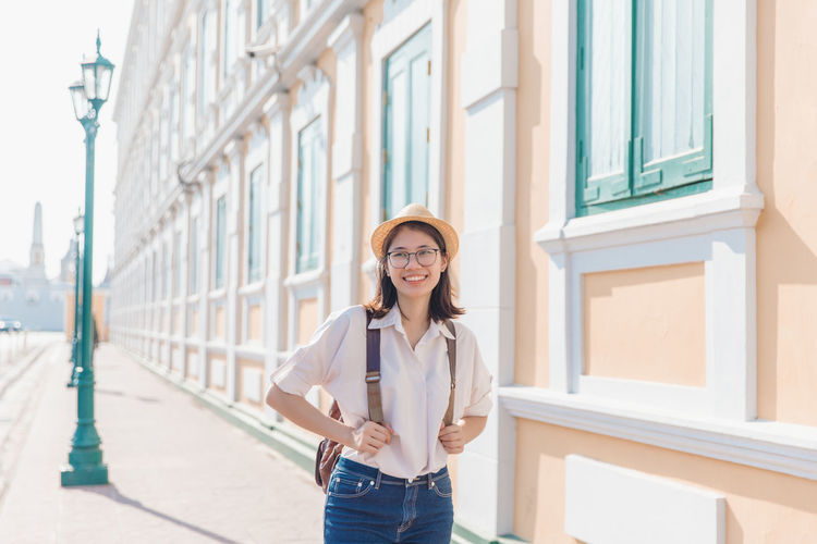Portrait of smiling young woman standing against building in city
