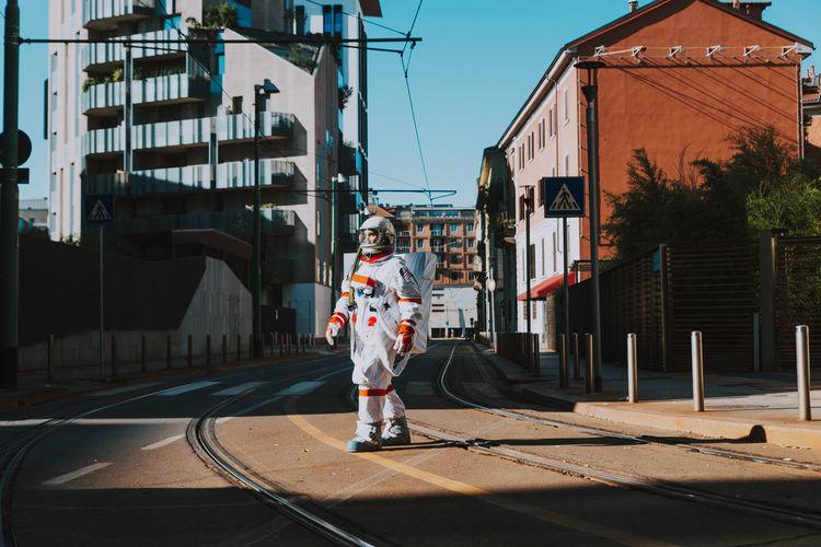 Full length of boy standing on street against buildings in city