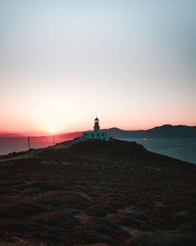 Lighthouse on beach against sky during sunset