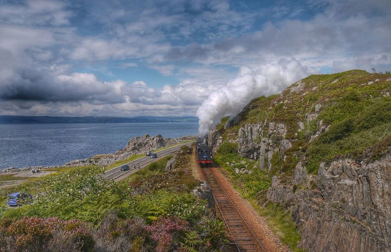 High Angle View Of Steam Train By Rock Formations Leading Towards Sea