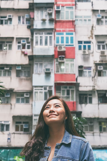 Portrait of beautiful woman standing against buildings in city