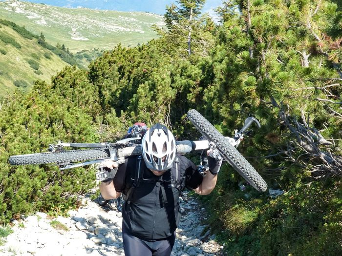Man Carrying Bicycle Over Shoulders On Trail During Sunny Day