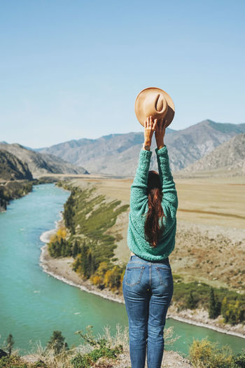 Young brunette woman traveller in sweater with felt hat on background of turquoise katun river