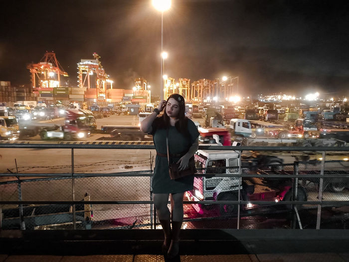 Portrait of smiling man standing in harbor at night