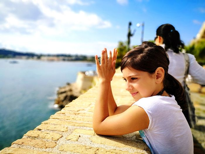 Side view of girl standing at railing on promenade against sky