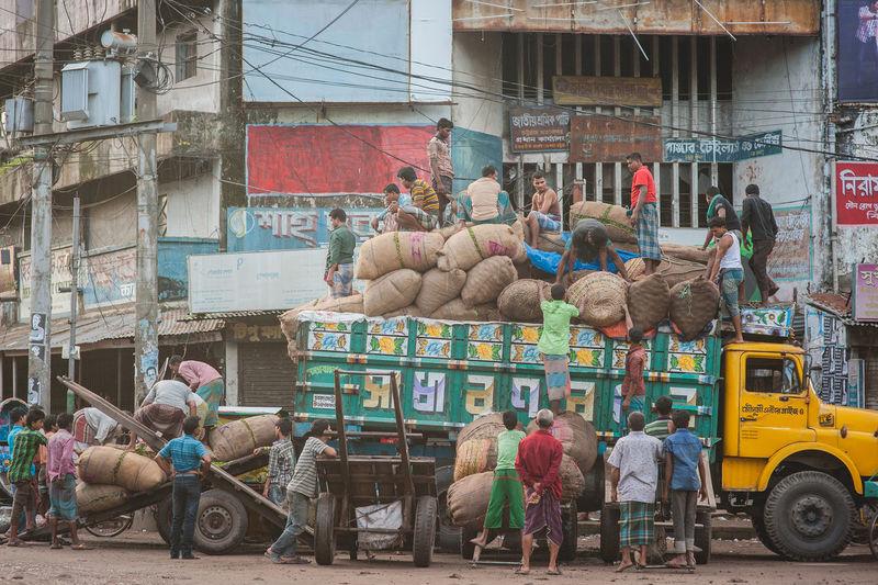 Men Loading Sacks On Truck Against Building