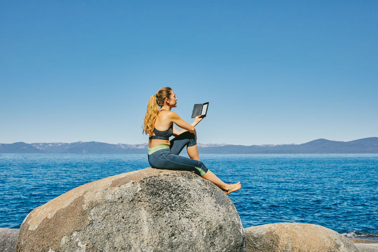 Woman sitting on rock by sea against clear sky