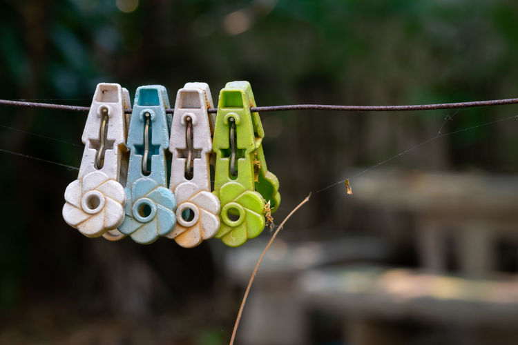 Close-up of clothespins hanging on rope