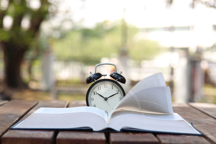 Close-up of alarm clock on book at table