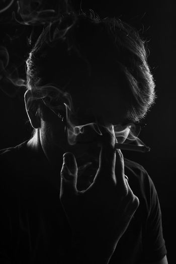 Close-Up Of Man Holding Cigarette Against Black Background
