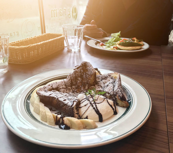 Nagoya, Japan - February 16, 2019: Chocolate french toast with a dish of salad eaten by a man in Gram Cafe and Pancakes on a table near the window Food And Drink Plate Food Table Ready-to-eat Freshness Indoors  Serving Size Indulgence Healthy Eating Still Life Meal No People Wellbeing Bread Close-up Day High Angle View Temptation Drink Glass Garnish Snack Breakfast Table Knife Gram Pancakes French Toast Cream Banana Eating Salad Sweet Dessert Japan Nagoya Restaurant