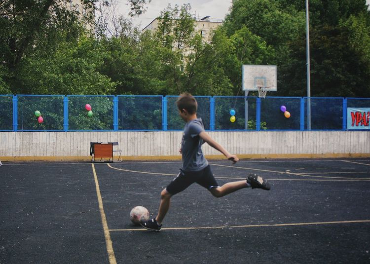 Full length of a boy playing with ball in the background