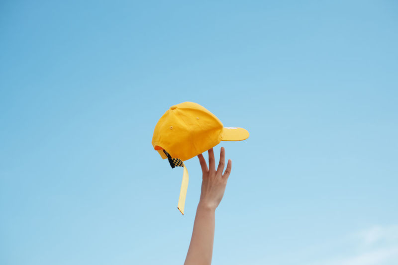 Low angle view of person holding umbrella against blue sky