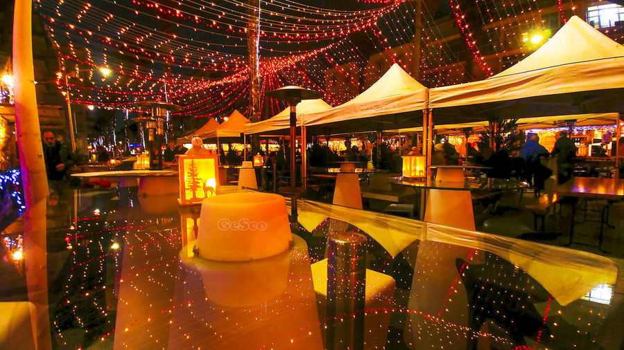 Christmas Market Illuminated Night Architecture Lighting Equipment Arts Culture And Entertainment Incidental People Built Structure Restaurant Amusement Park Reflection Business Food And Drink Group Of People City Outdoors Amusement Park Ride Glass - Material Travel Destinations Luxury