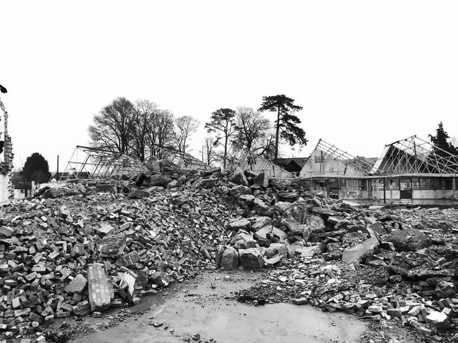 Damaged Destruction Tree Built Structure Building Exterior Abandoned Outdoors Natural Disaster Day Real People Demolished Clear Sky Architecture Sky Demolition Zone Monochrome Photography Rubble