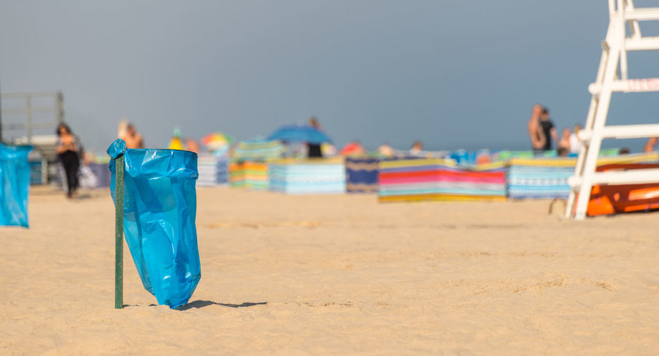 An empty garbage bag on the beach on a sunny summer day, in the background people, a beach screen