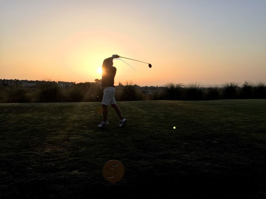 Golfing Sunset Leisure Activity Full Length Sun Lifestyles Clear Sky Field Holding Playing Tranquility Park - Man Made Space Scenics Beauty In Nature Tranquil Scene Nature Lens Flare Outdoors Sunbeam Non-urban Scene Carefree Golf