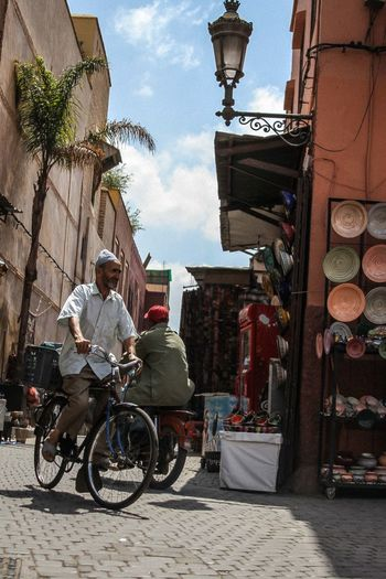 Ancient Civilization Architecture Bicycle Building Exterior Built Structure Culture Cultures Damaged Day Land Vehicle Marrakech Men Mode Of Transport Morocco Real People Religion S Sitting Spirituality Stationary Streetphotography Transportation Traveling Women Wood