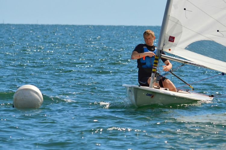 Man sailing on sailboat in sea during race