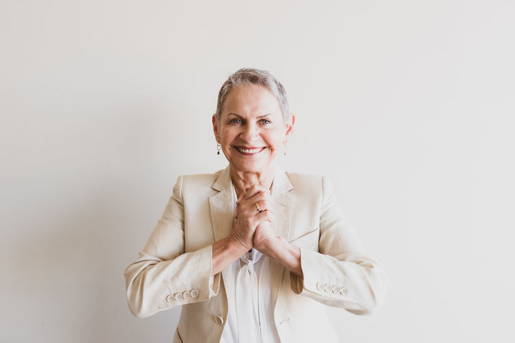 Waist up view of senior woman in cream jacket with hands clasped togther - consensus concept (selective focus) Agreement Attractive Background Beautiful Beige Cheerful Clasped Consensus Copy Space Cream Elderly Grey Hair Hands Happy Jacket Leadership Mature Neutral Old Older  Professional Senior Short Hair Smart Smart Casual Smiling Team Building Together Waist Up Wall Woman Looking At Camera One Person Front View Happiness Standing Studio Shot