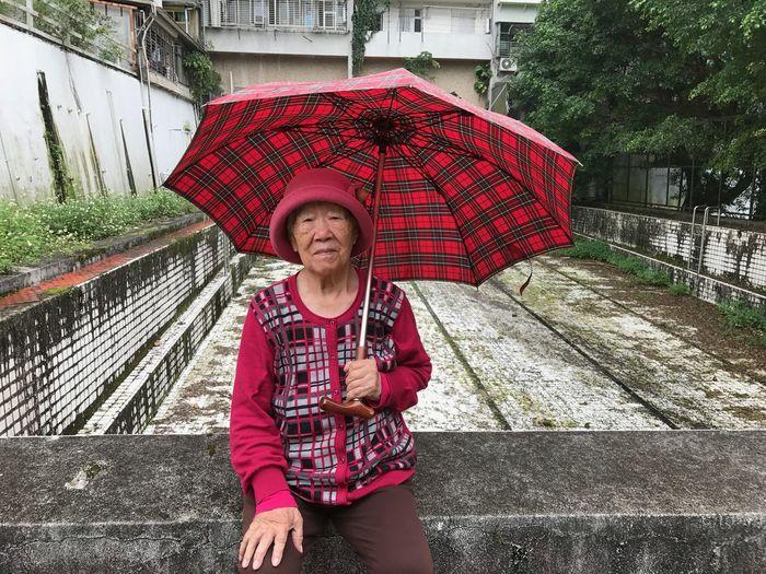 Portrait of woman holding umbrella against built structure